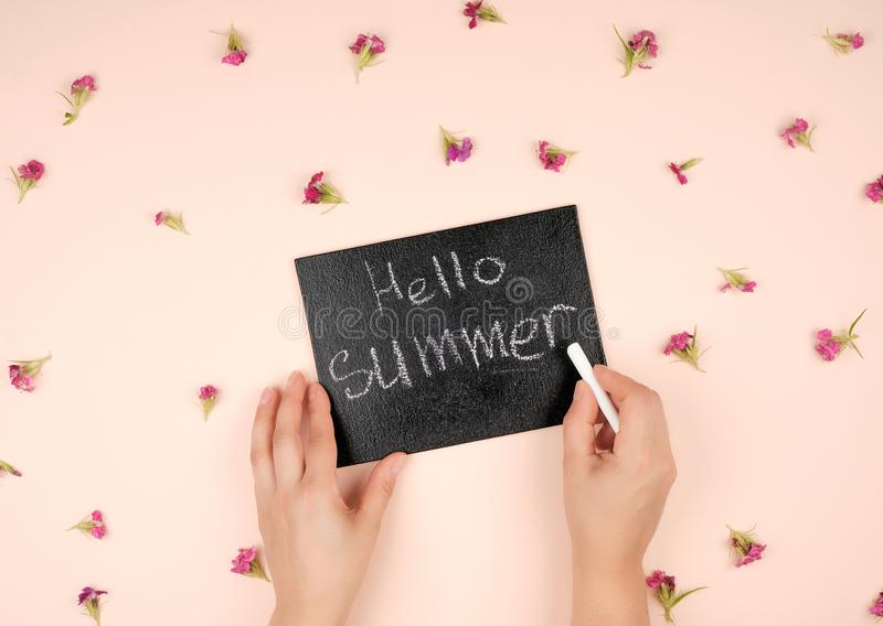 black chalk frame with an inscription hello summer and two female hands stock photos