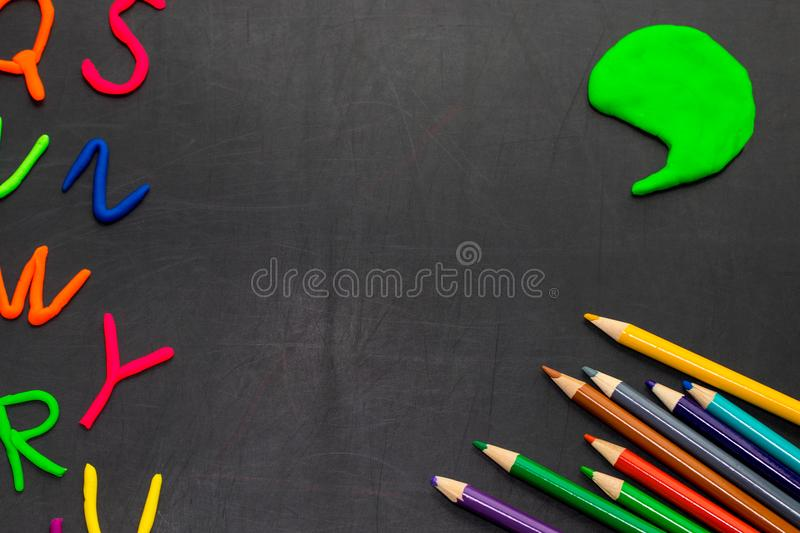 Black chalkboard with colorful pencils and letters, concept for royalty free stock photo