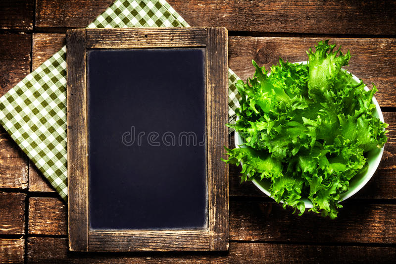 Black chalkboard for menu and fresh salad over wooden background. Diet Food Restaurant and healthy lifestyle concept stock images