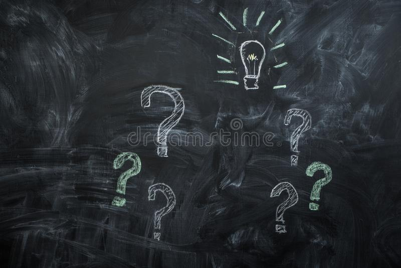 Drawn on black chalkboard question marks and light bulb royalty free stock images