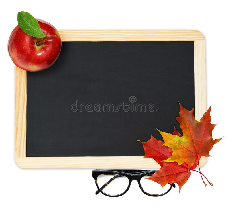 Black chalkboard , red maple leaves, apple and glasses royalty free stock images