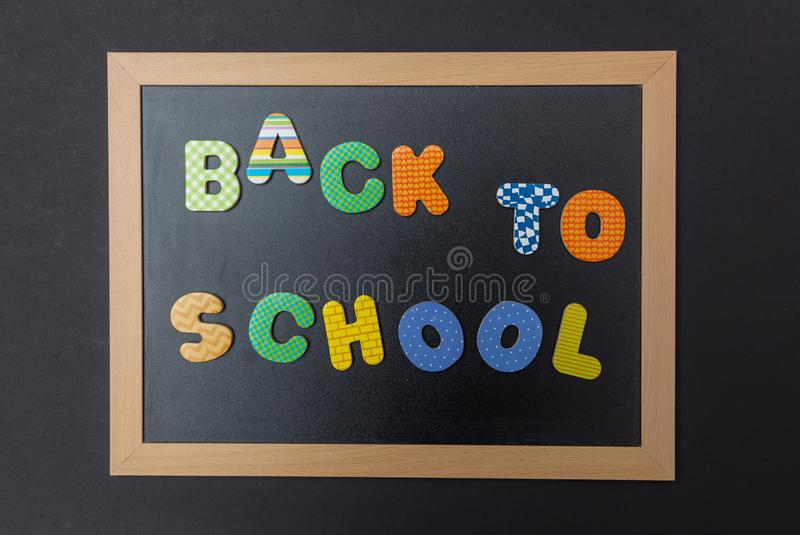 Black chalkboard with wooden frame, text back to school in colorful letters, black wall background stock image