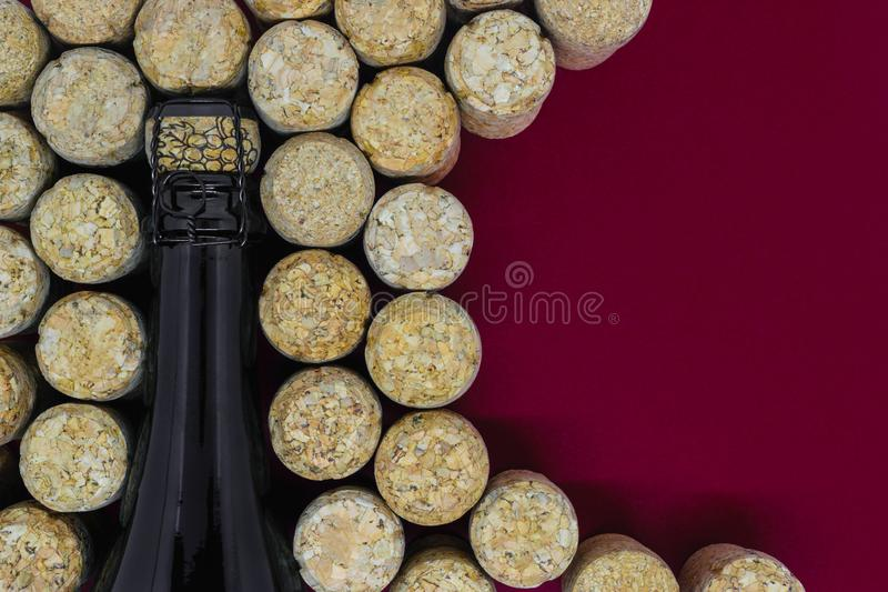 Black champagne bottle surrounded of many champagne corks. On red background with copy space royalty free stock photography