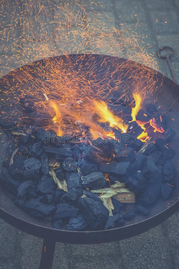 Black Charcoal With Fire on Black Round Steel Bowl stock photography