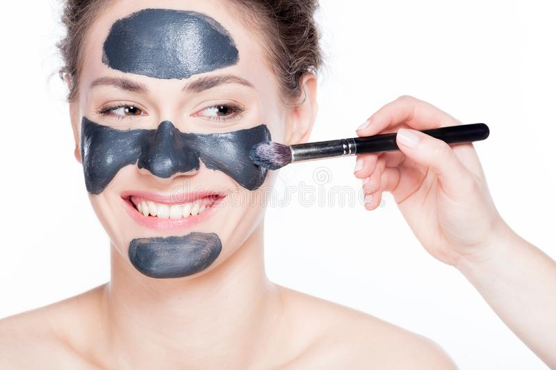 Black charcoal mask application on beautiful woman. Young beautiful woman is having a black charcoal mask applied on her skin. Smiling, authentic girl portrait stock images