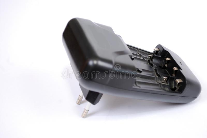 The black charger for charging of AA and AAA rechargeable batteries a white background. stock photo