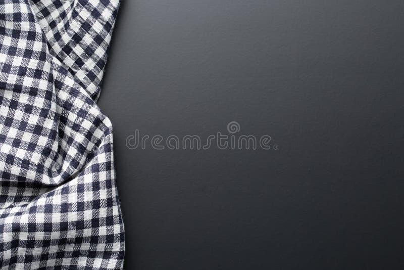 Black checkered napkin on table. Black checkered napkin on black table royalty free stock photo