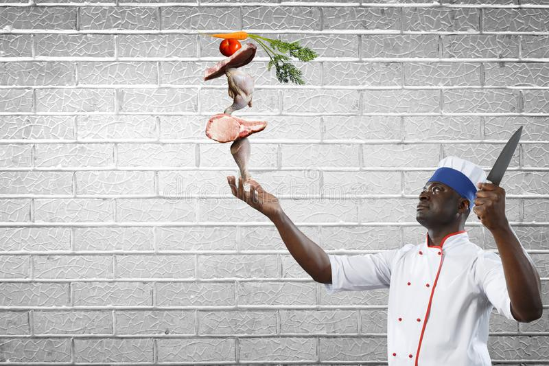 Black chef creative cooking. Mixed media. Black man self confident, holding a big kitchen knife with ingredients build into pyramid on his hand, white brick stock images