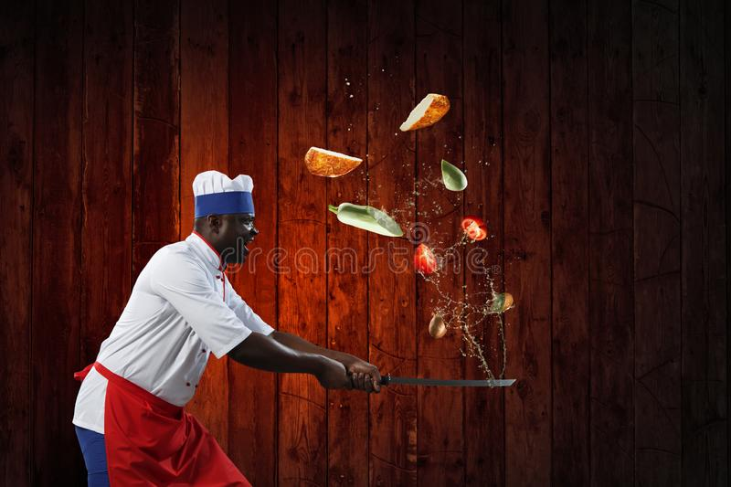 Black chef creative cooking. Mixed media. Black man triumphant, dramatic and victorous, holding a big kitchen knife with chopped vegetables and fruit around him royalty free stock image