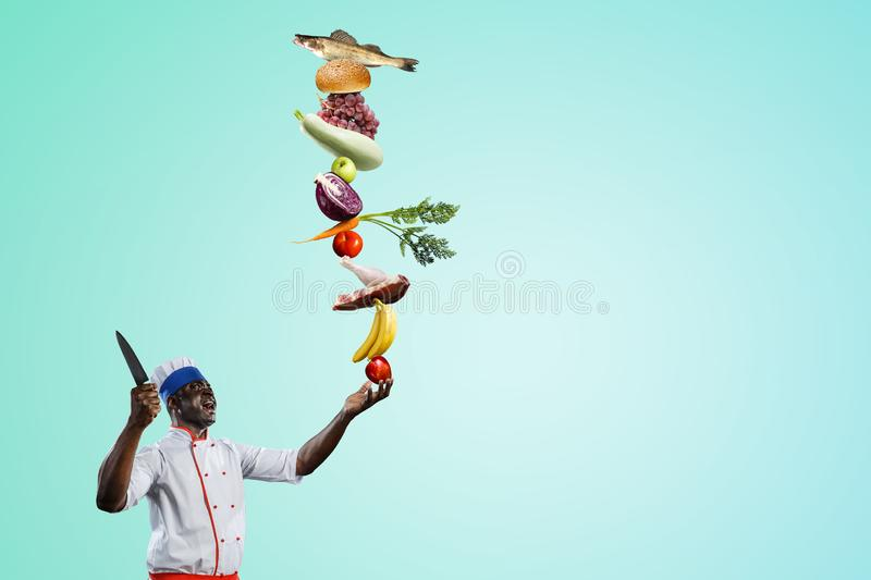 Black chef creative cooking. Mixed media. Black man self confident, holding a big kitchen knife with ingredients build into pyramid on his hand, isolated stock photography