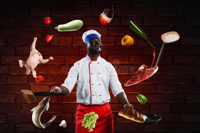 Black chef creative cooking. Mixed media. Smiling black man in uniform, holding a frying pan and a kitchen knife, with ingredients around him, brick wall royalty free stock images