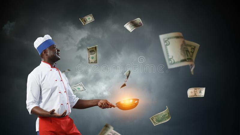 Black chef creative cooking. Mixed media. Black smiling man holding two frying pans with dollar banknotes around him, dark sky background royalty free stock image