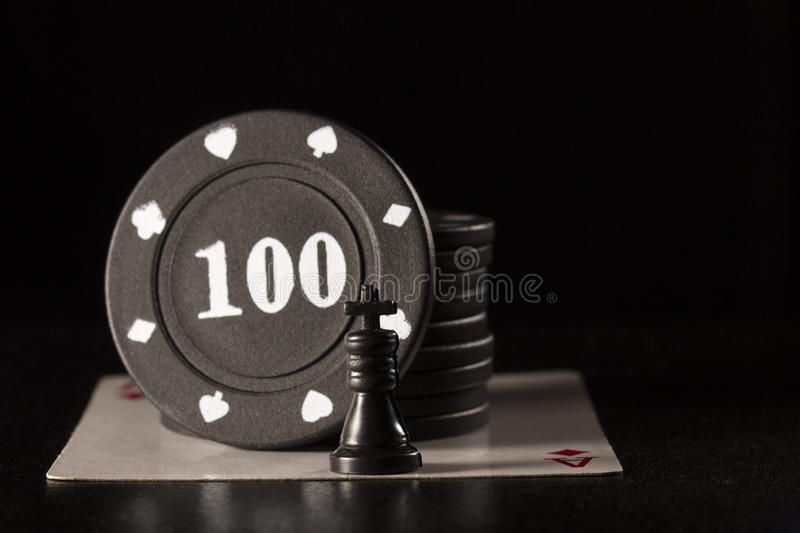 Black chess king and poker chips on ace of diamonds royalty free stock photo