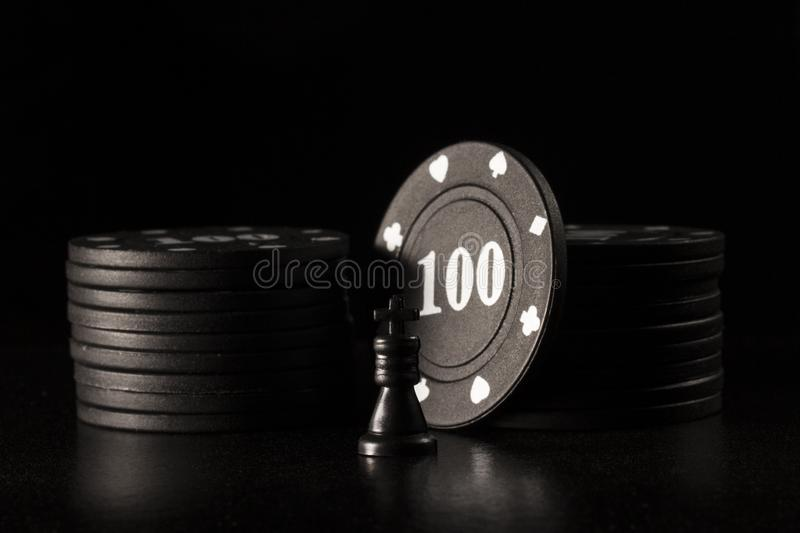Black chess king and poker chips on a dark background stock photos
