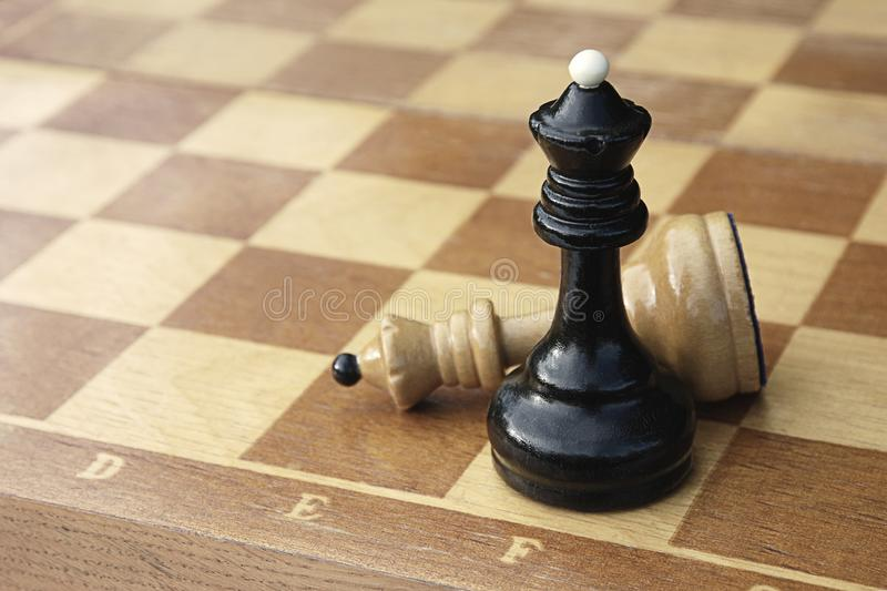 Two chess kings on wooden chess board. White figure lying defeated next to black winner. Black chess king put checkmate to white king. Two chess pieces on wooden royalty free stock images