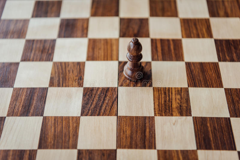 Black chess piece on wooden chessboard. High angle view of black chess piece on wooden chessboard stock images