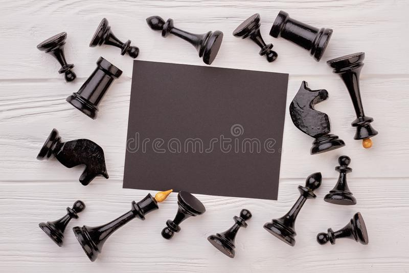 Black chess pieces and blank paper card. Chess figures and black paper sheet lying on white background royalty free stock photo