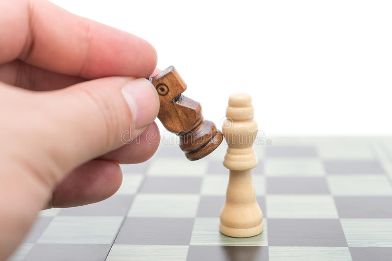 Black chess player knocks down the white king. With his Knight stock images