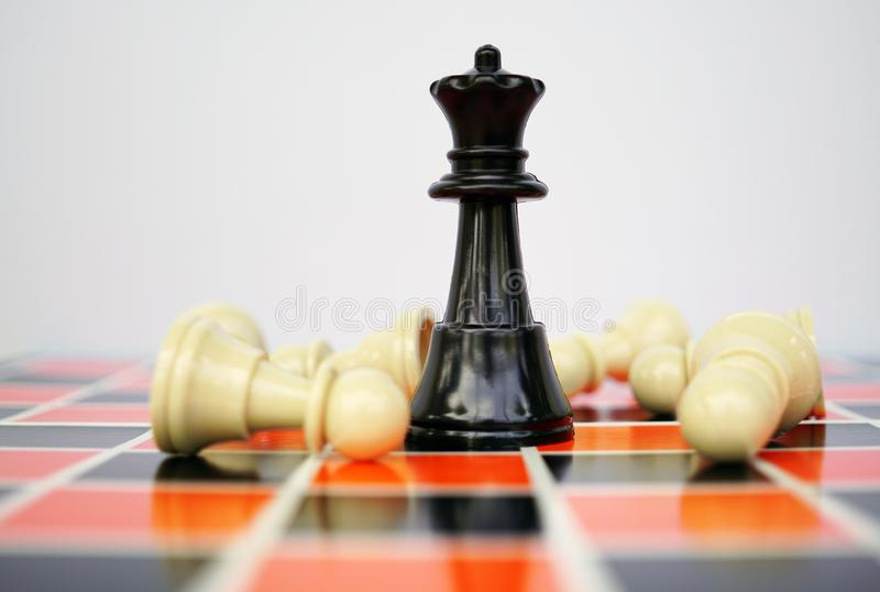 Black chess Queen with white pawns stock photo