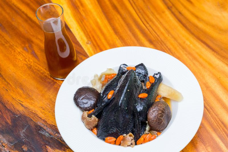 Black chicken Soup on wood dish stock photography
