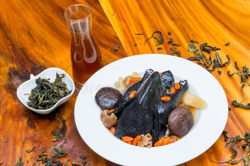 Black chicken Soup on wood dish royalty free stock images