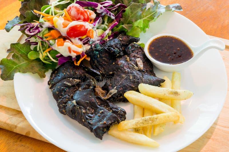 Black chicken steak on table stock photo