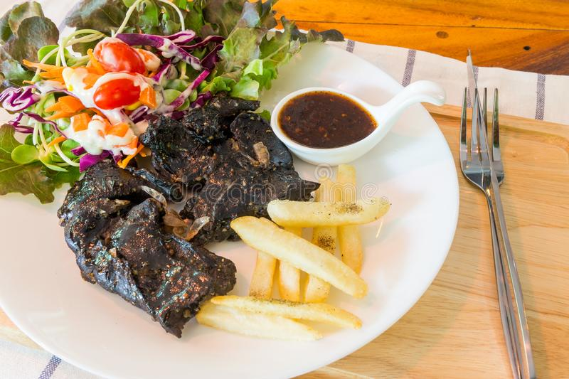 Black chicken steak on table royalty free stock images