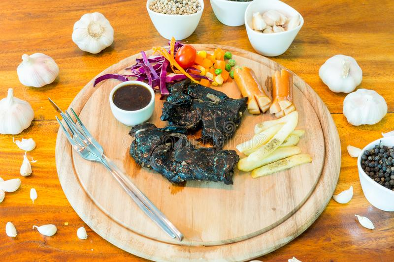 Black chicken steak on table stock photos