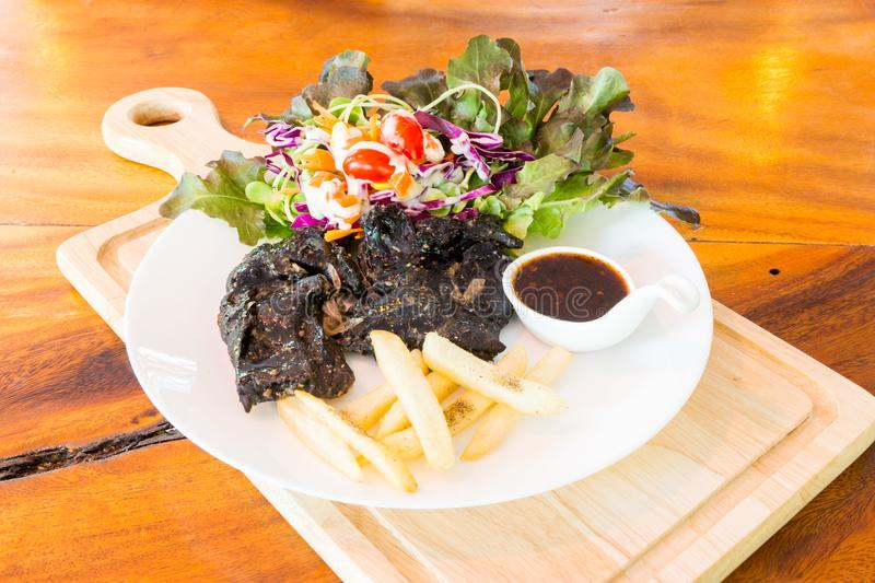 Black chicken steak on table royalty free stock photos