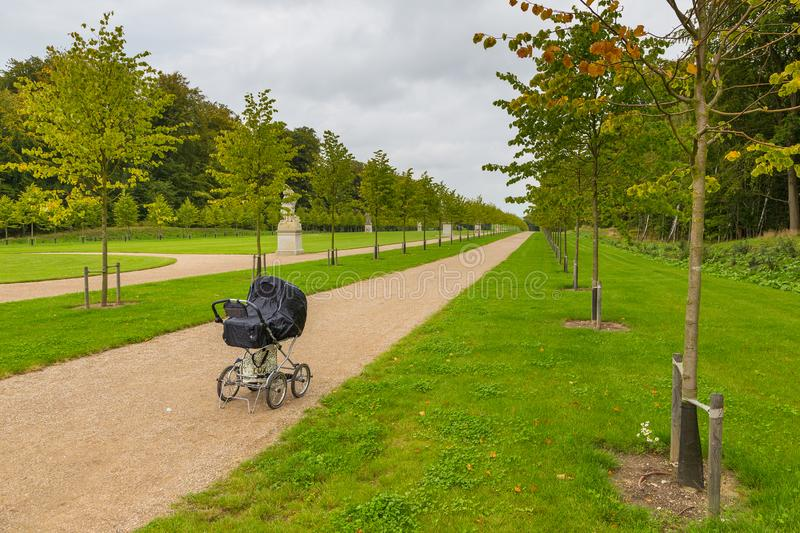 Black children`s carriage on the avenue in the Palace Garden, Fredensborg, Denmark. Black children`s carriage on the avenue in the Palace Garden. The largest royalty free stock images