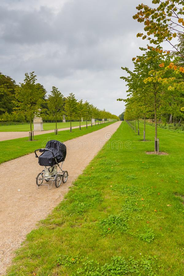 Black children`s carriage on the avenue in the Palace Garden, Fredensborg, Denmark. Black children`s carriage on the avenue in the Palace Garden. The largest stock photos