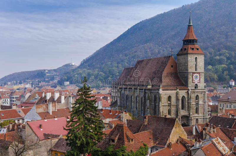 The Black Church in Brasov, Romania. The Black Church pictured from atop surrounded by old houses and Mount Tampa in the background in Brasov, Romania stock image