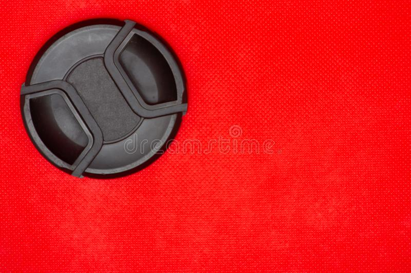Black circle lens cap for DSLR camera lens on a rich red background. Close up of a black circle lens cap top left corner for DSLR camera lens on a rich red royalty free stock photo