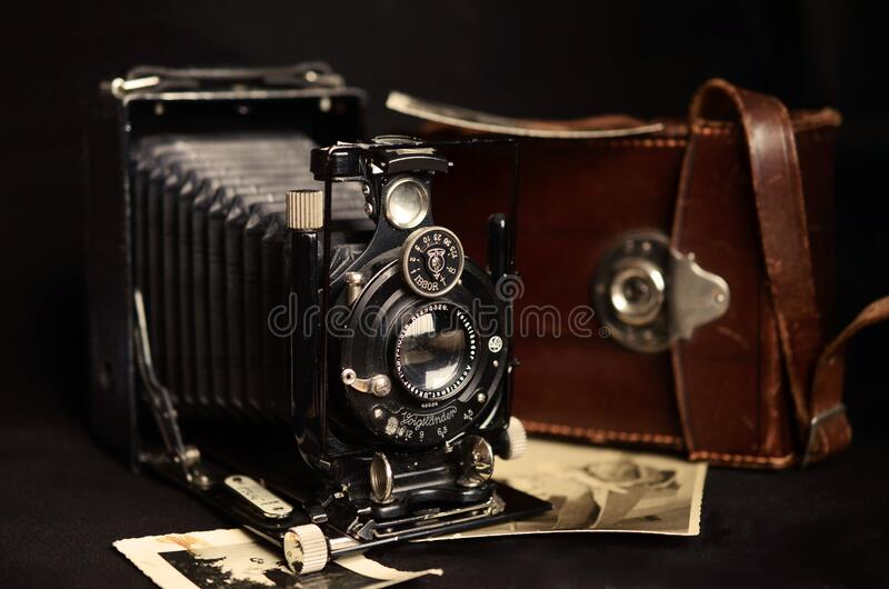 Black Classic Camera Near Brown Leather Bag stock photography