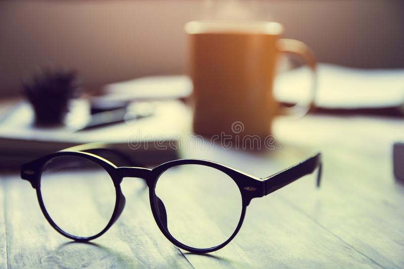 Black classic eyeglasses and books ,yellow cup hot coffee on wood table, in Monday morning, first week of work . Vintage tone with sun light,Selective focus stock photos