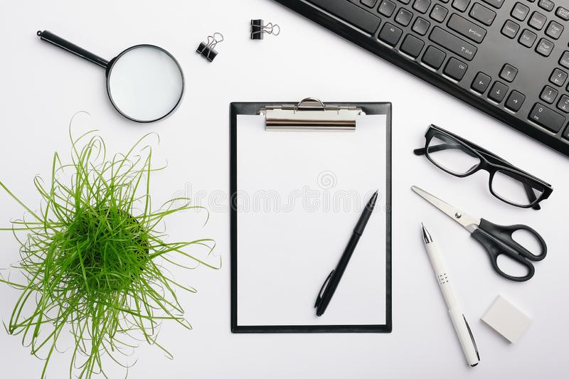 Black clipboard mockup. desk workspace with black keyboard, glasses, pens, eraser and other office accessories royalty free stock image