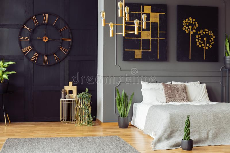 Black clock, golden chandelier, paintings and white bed in an elegant bedroom interior. Real photo. Concept stock photo