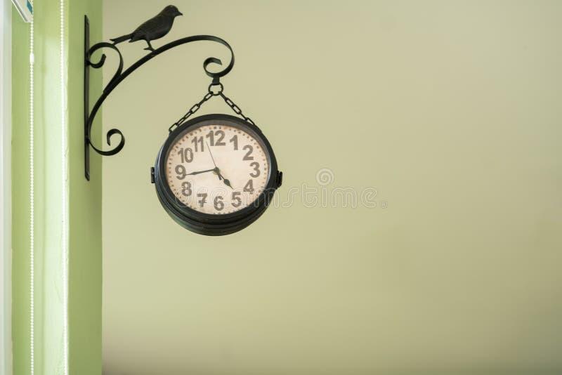 Black clock hanging at the wall royalty free stock image