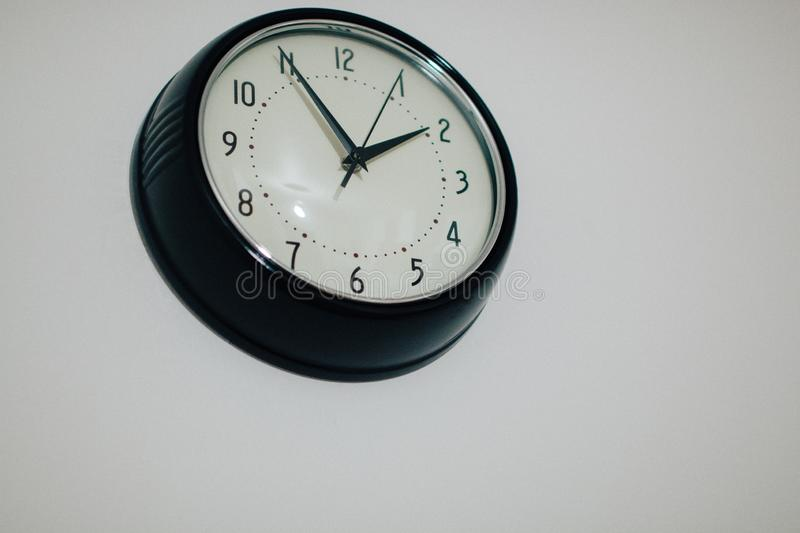 Black clock hanging on wall stock photos