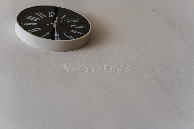 Black clock hanging on the white wall royalty free stock photos