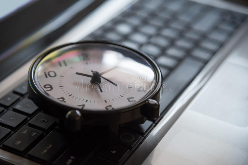 Black clock lay on keyboard time metaphor concept in dark low key tone, selective focus. stock photos