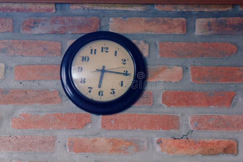 The black clock is on the old brick wall royalty free stock image