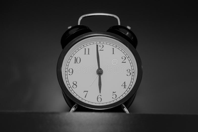 Black clock on a shelf.Style Black & White. royalty free stock images