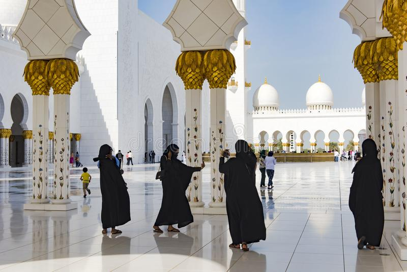 Black clothed women in hijab taking selfies in great mosque, Sheikh Zayed Grand Mosque, Abu Dhabi. In traditional culture clothed women wearing black hijab in stock photos
