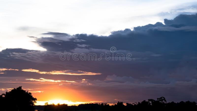 Dark cloudy sky background over the sunset in the evening sky in the countryside of Thailand. royalty free stock photo