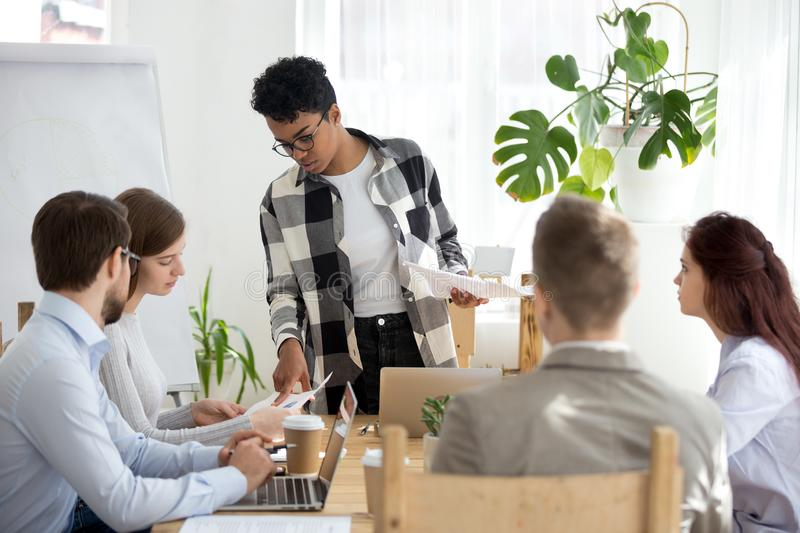 Black coach woman presenting report to colleagues in office. Diverse millennial businesspeople company sitting at seminar presentation in office boardroom Black stock images