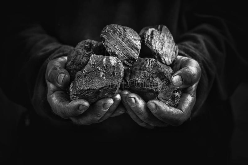 Black coal in the hands, heavy industry, heating. Mineral raw materials stock image