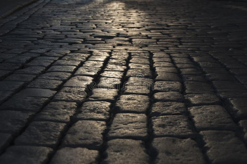 Black cobbled stone road background with reflection of light seen on the road. Black or dark grey stone pavement texture. Light on the stone pavement royalty free stock photography