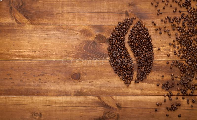 Black coffee in bean seed shape and scattered on brown wooden table, dark cofee espresso roasted grain flavour aroma cafe, natural royalty free stock images