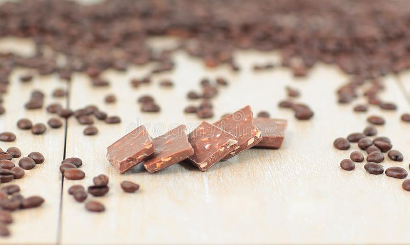 Black coffee beans and chocolates on wooden background stock image